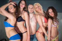 A bald man hugging four beautiful girls Royalty Free Stock Photo