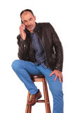 Bald man in leather jacket posing seated Royalty Free Stock Photo