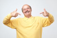 Bald man looking confident with smile on face, pointing himself with fingers royalty free stock photo