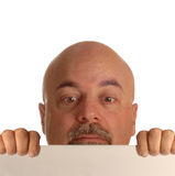 Bald man looking over sign. Bald man holding up blank sign and straining to look over it Royalty Free Stock Images