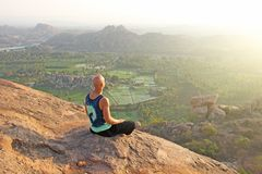 A bald man looks at the sunset at Hampi. Top Hampi. A man sits on top of a mountain and looks into the distance. Meditation, rest. Harmony, alone with nature royalty free stock photography