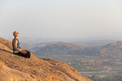 A bald man looks at the sunset at Hampi. Top Hampi. A man sits on top of a mountain and looks into the distance. Meditation, rest. Harmony, alone with nature royalty free stock photos