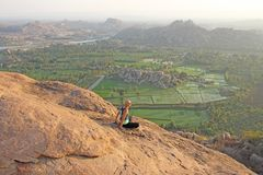 A bald man looks at the sunset at Hampi. Top Hampi. A man sits on top of a mountain and looks into the distance. Meditation, rest. Harmony, alone with nature stock photo