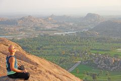 A bald man looks at the sunset at Hampi. Top Hampi. A man sits on top of a mountain and looks into the distance. Meditation, rest. Harmony, alone with nature stock photography