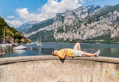 Bald man lying down on the shore of Como lake, in front of the Lecco town, with mountain in background. Royalty Free Stock Photos
