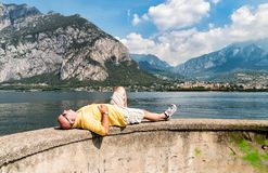 Bald man lying down on the shore of Como lake, in front of the Lecco town, with mountain in background. Stock Photography