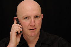Bald man on mobile phone. A bald man talking on a mobile phone, black background Royalty Free Stock Image