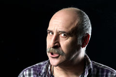 Bald Man with Mustaches Very Angry. Portrait of annoyed bald man with a big mustache expressing anger Stock Photo