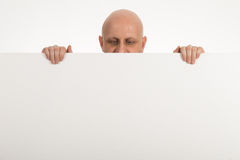 Bald man peeps over top of blank white paper Royalty Free Stock Photos