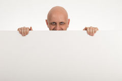 Bald man peeps over top of blank white paper Stock Photography