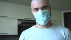 Bald Man In Protective Mask At Home. Seriously Looks At The Camera. Epidemic, Pandemic, Self-isolation. Home Mode