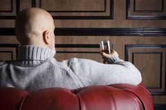 Bald man in the red armchair Stock Images