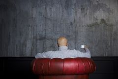 Bald man in the red armchair Royalty Free Stock Image