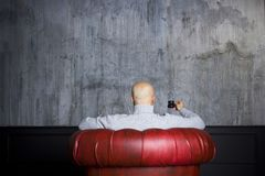 Bald man in the red armchair Royalty Free Stock Photos