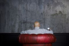 Bald man in the red armchair Royalty Free Stock Images
