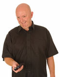 Bald man with remote. A bald man with TV remote controller in hand Royalty Free Stock Images