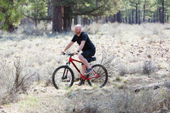 Bald man riding a mountain bike on a dirt trail in the forest Stock Photography