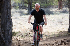 Bald man riding a mountain bike on a dirt trail in the forest Royalty Free Stock Photos