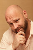 Bald man rubbing his chin Royalty Free Stock Photography
