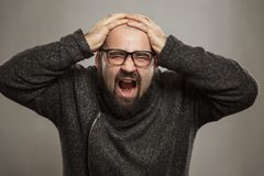 Bald man screaming, clutching his head. Horizontal emotion portrait stock photo