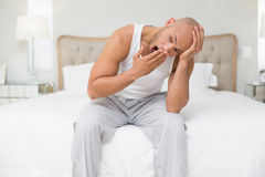Bald man sitting and yawning in bed Stock Photo