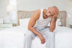Bald man sitting and yawning in bed Stock Image