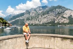 Bald man with smartphone sitting on the shore of Como lake in Italy Stock Photo