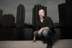 Bald man squatting. With the city at night in the background Stock Photography