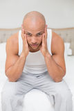 Bald man suffering from headache in bed Stock Image