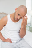Bald man suffering from headache in bed Royalty Free Stock Photos