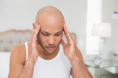 Bald man suffering from headache in bed Stock Images