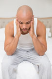 Bald man suffering from headache in bed Royalty Free Stock Photography