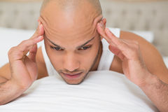 Bald man suffering from headache in bed Stock Photos