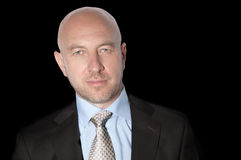 Bald man in a suit and tie. On a black background Stock Image