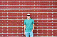 The bald man in sunglasses against the background of a red brick wall Royalty Free Stock Image