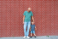 The bald man in sunglasses and the little boy against the background of a red brick wall Stock Image