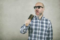 Bald man with sunglasses singing a hair brush stock image