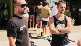 Bald man in sunglasses stands next to young man in black jersey on summer day. Mature bald man in sunglasses and t-shirt stands next to young attractive guy stock footage