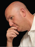 Bald man thinking. Portrait of a bold man thinking, black background stock images