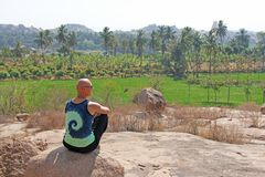 Bald Man is a tourist and photographer in Hampi, sits on a rock and looks into the distance. Large stones Hampi on the side of the. Village of Anegundi and royalty free stock image