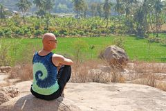 Bald Man is a tourist and photographer in Hampi, sits on a rock and looks into the distance. Large stones Hampi on the side of the. Village of Anegundi and royalty free stock photos