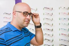 Bald man trying on glasses Stock Photography