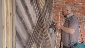 Bald man using a spray gun to paint the facade of the house. stock video footage