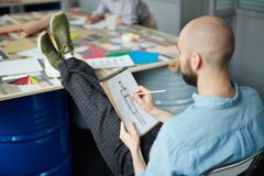 Bald man working on fashion sketch. Rear view of concentrated bald young man sitting on chair and keeping feet up on colorful table while working on fashion royalty free stock image