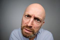 Bald mature guy in gray casual shirt discovering hidden camera. Hidden camera concept stock image