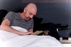 Bald middle aged man book Stock Images