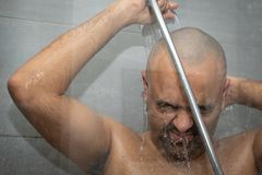 British Asian man taking a shower in the shower cubicle - with copy space. royalty free stock images