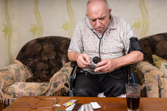 Bald Old Man Checking Medicines with BP Apparatus. Bald Middle Aged Man on his Wheelchair, Checking his Medicines While Holding a BP Apparatus at the Living Room Stock Image