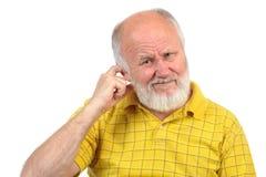 Bald senior man picking his ear Stock Photography