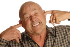 Bald senior man plugging ears. Bald senior man plugging his ears isolated on white background Royalty Free Stock Photos